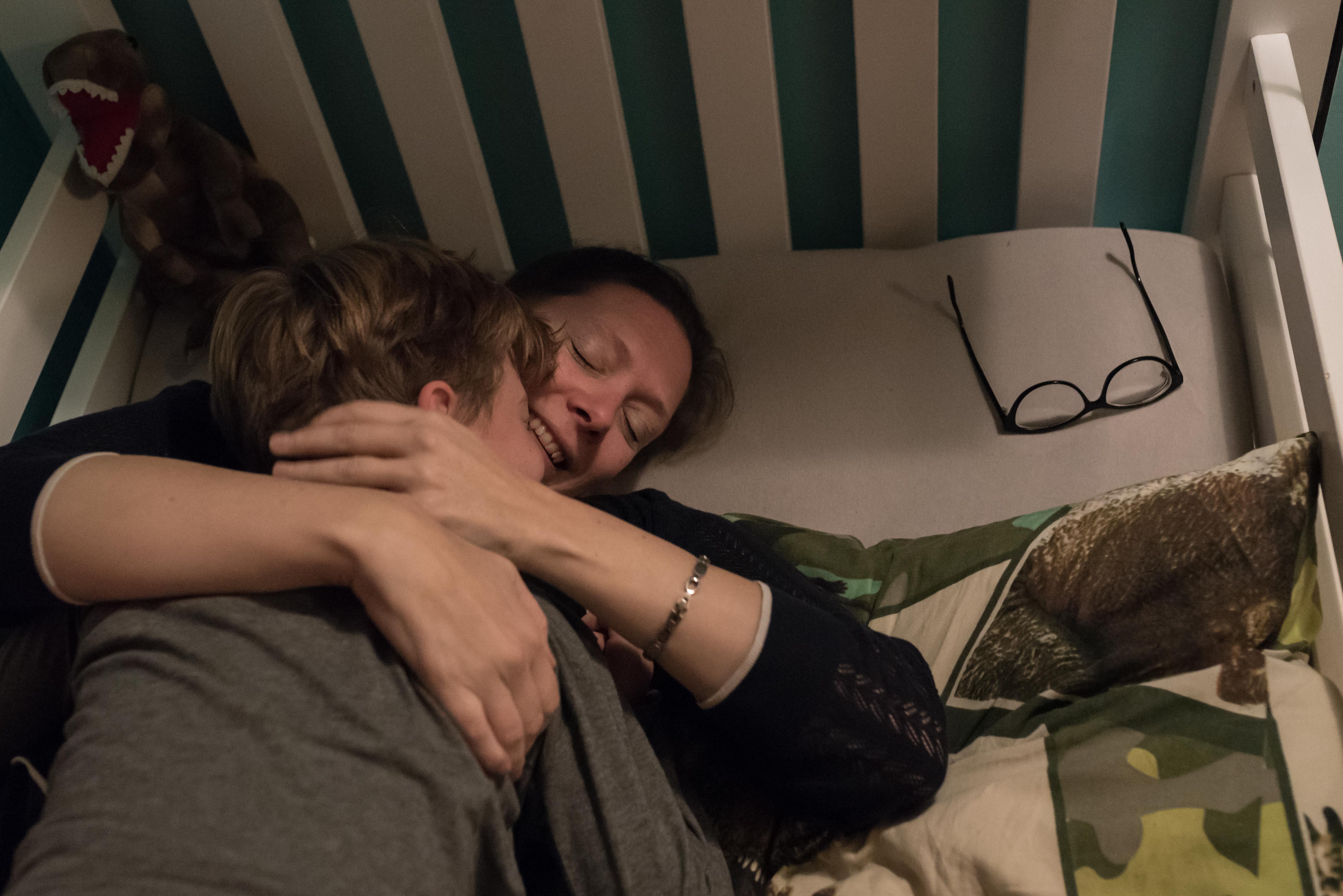 Moeder knuffelt haar zoon tijdens het naar bed brengen Jasja de Wit Fotografie
