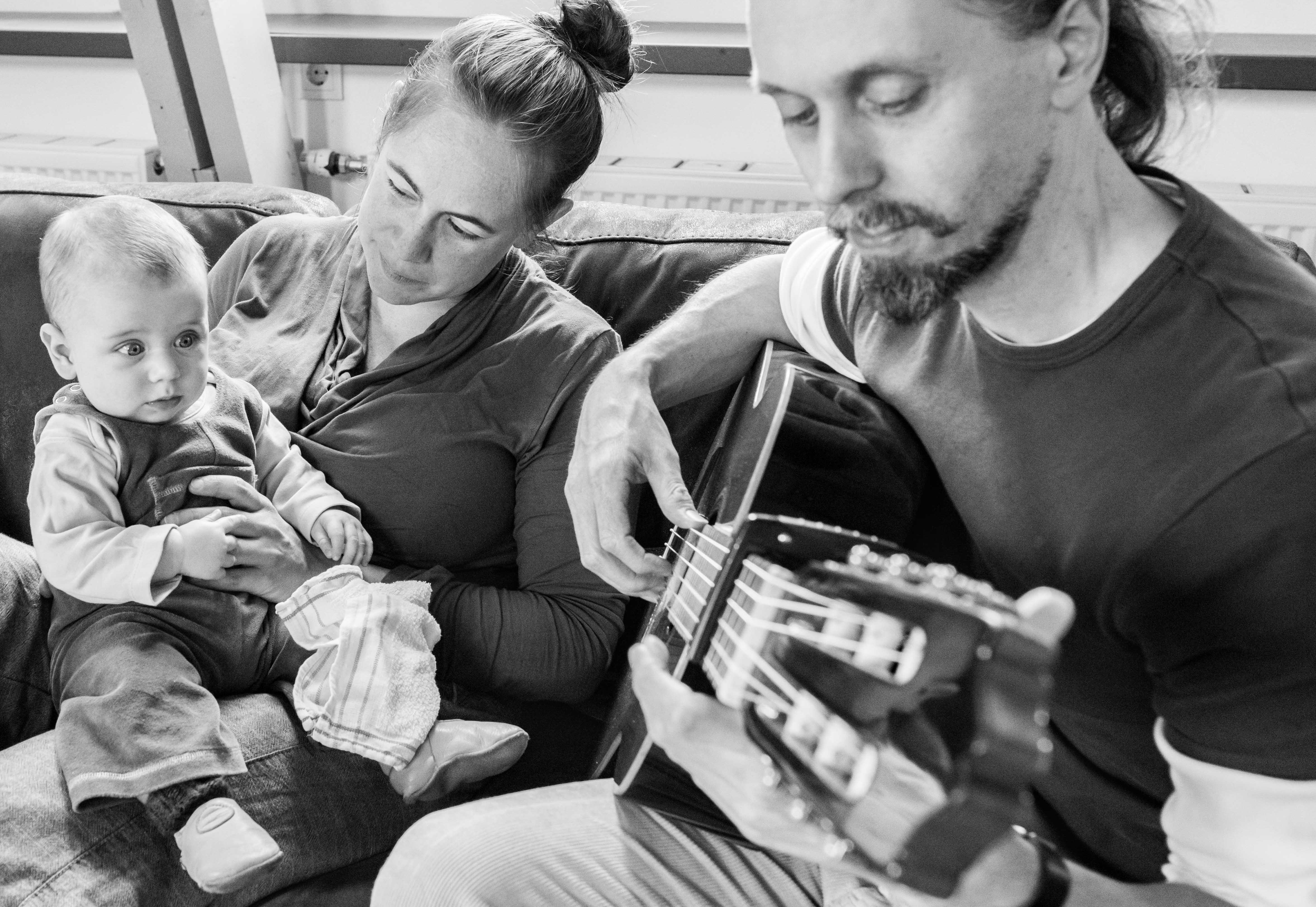 Vader speelt gitaar terwijl moeder en kind luisteren Jasja de Wit Fotografie