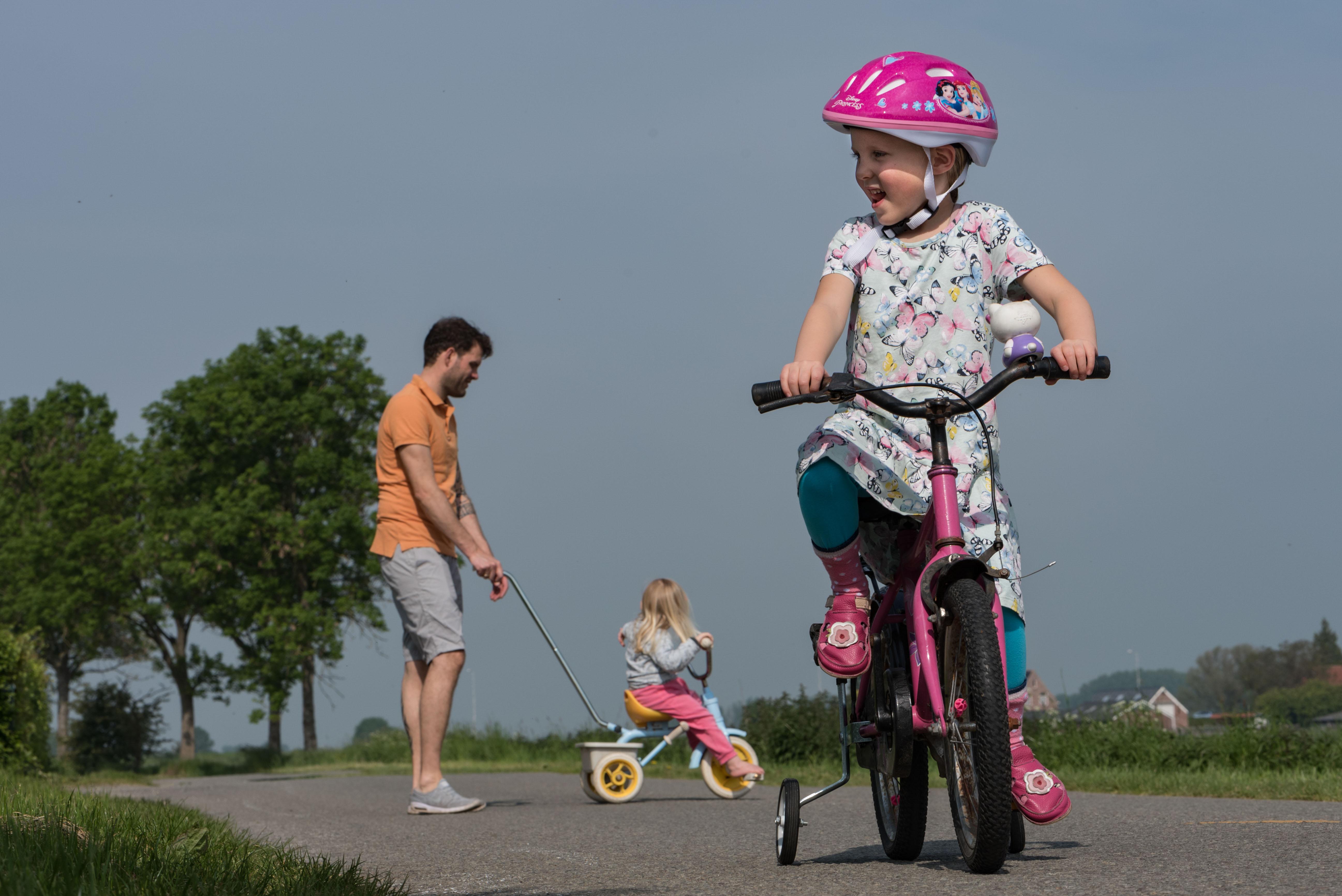 Meisje fietst op fiets met zijwieltjes Jasja de Wit Fotografie
