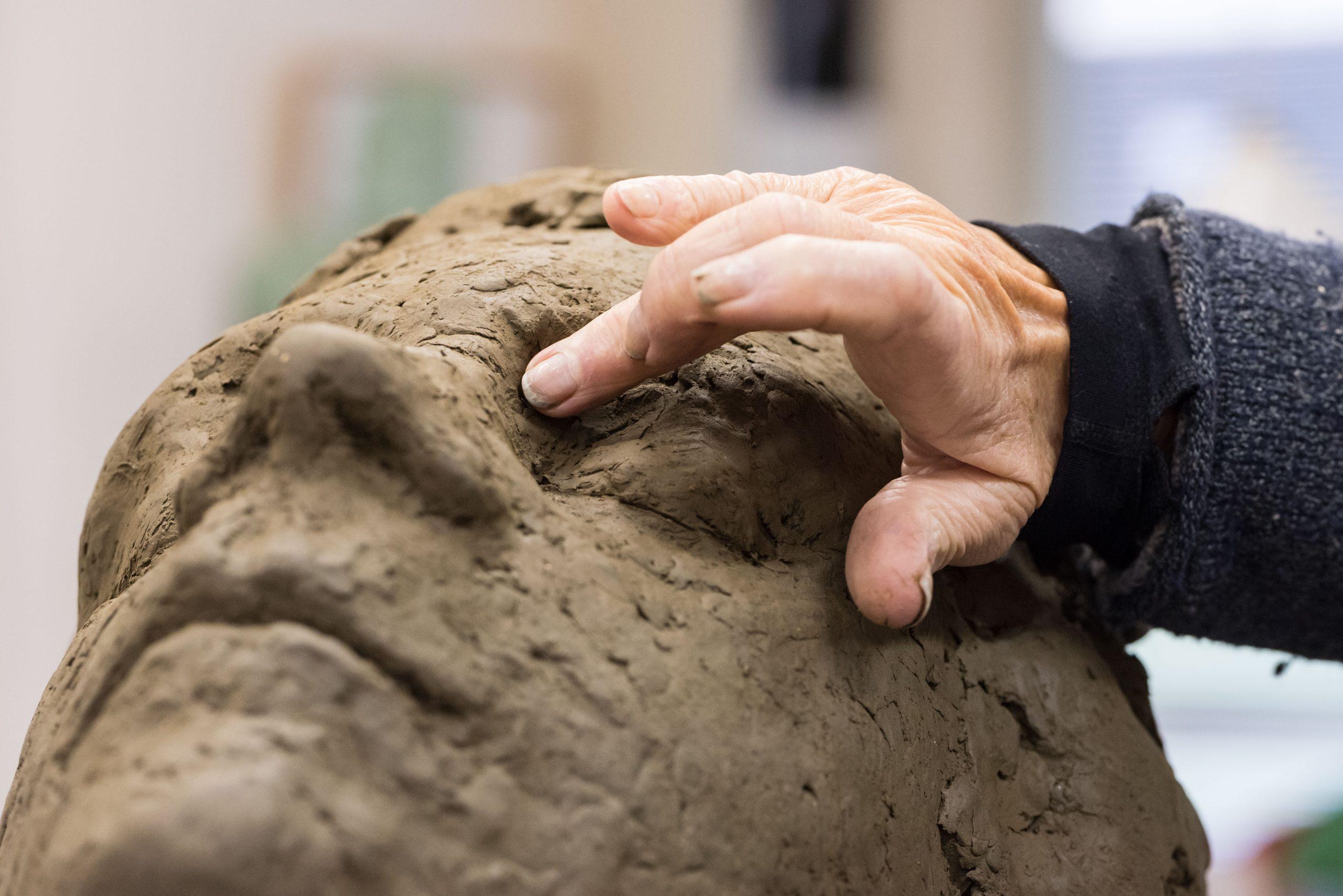 Maïté Duval werkt met haar hand het oog van een beeld in klei bij