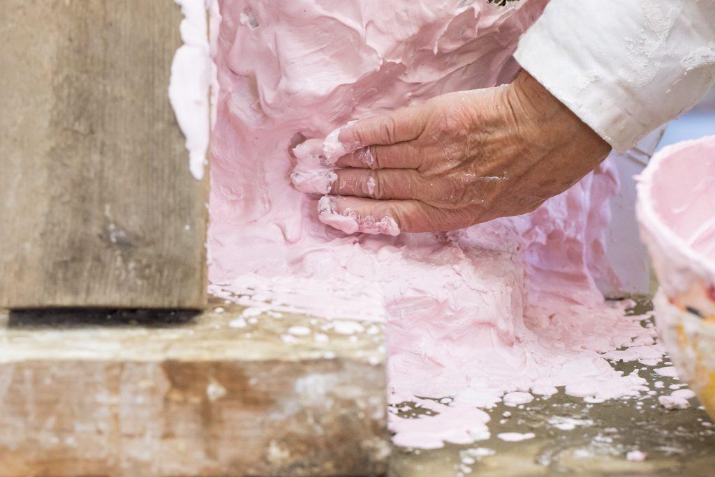 De hand van Maïté Duval brengt zorgvuldige roze gips aan op het beeld in klei