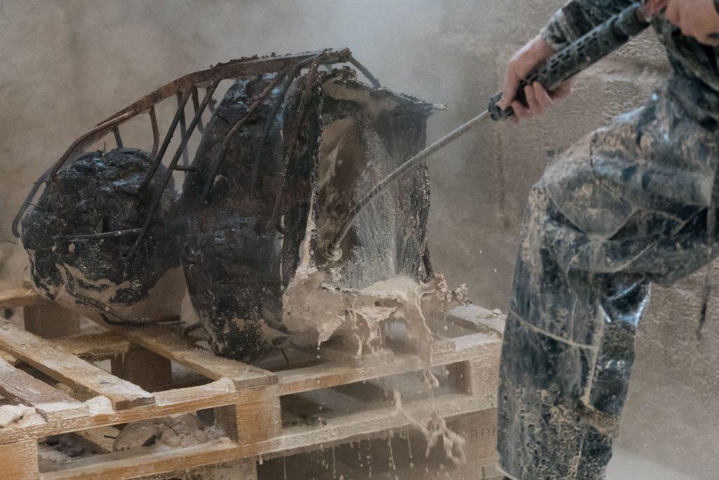 Man spuit gipsresten van bronzen beeld nadat het net gegoten is in brons