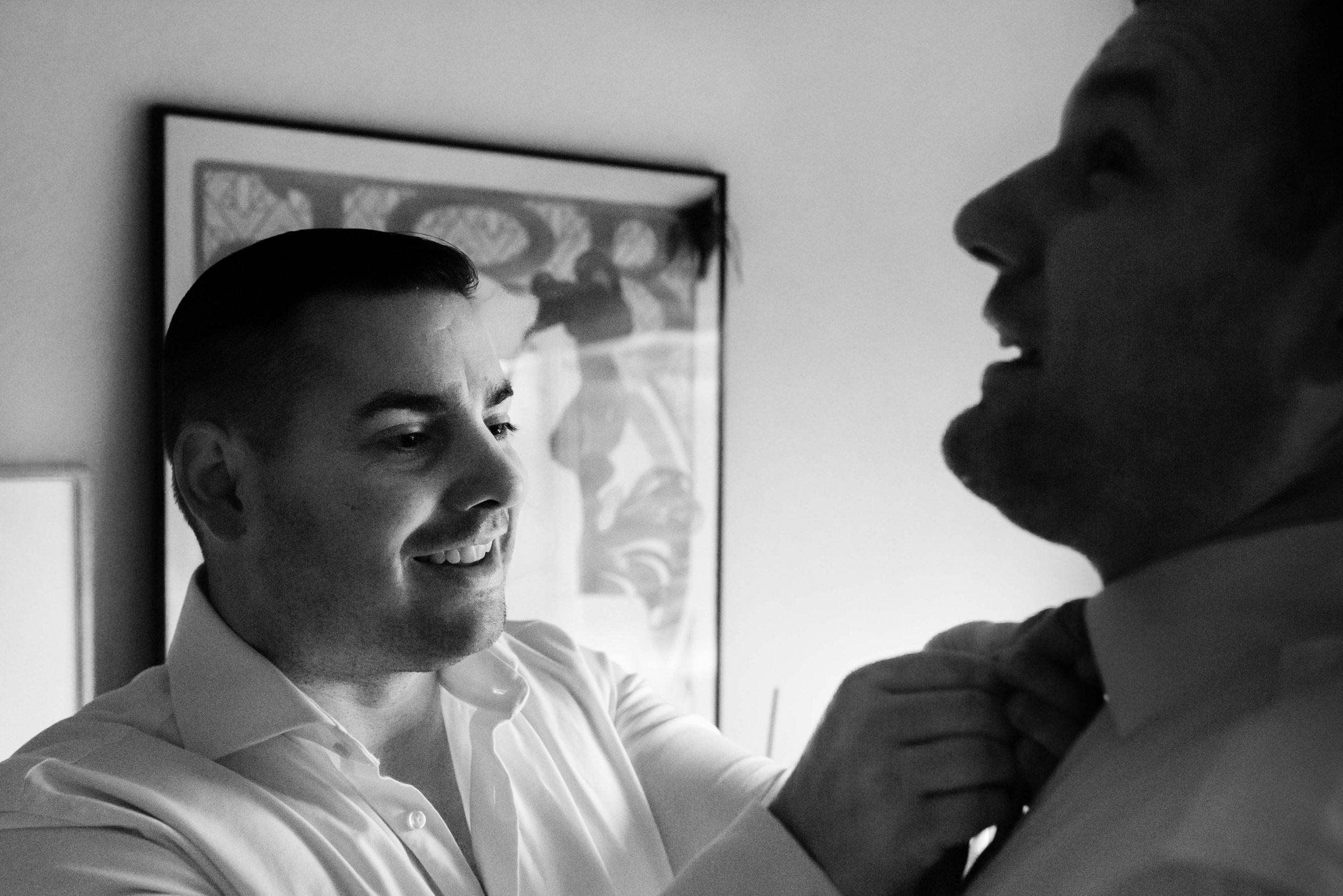Best man helpt bruidegom met stropdas