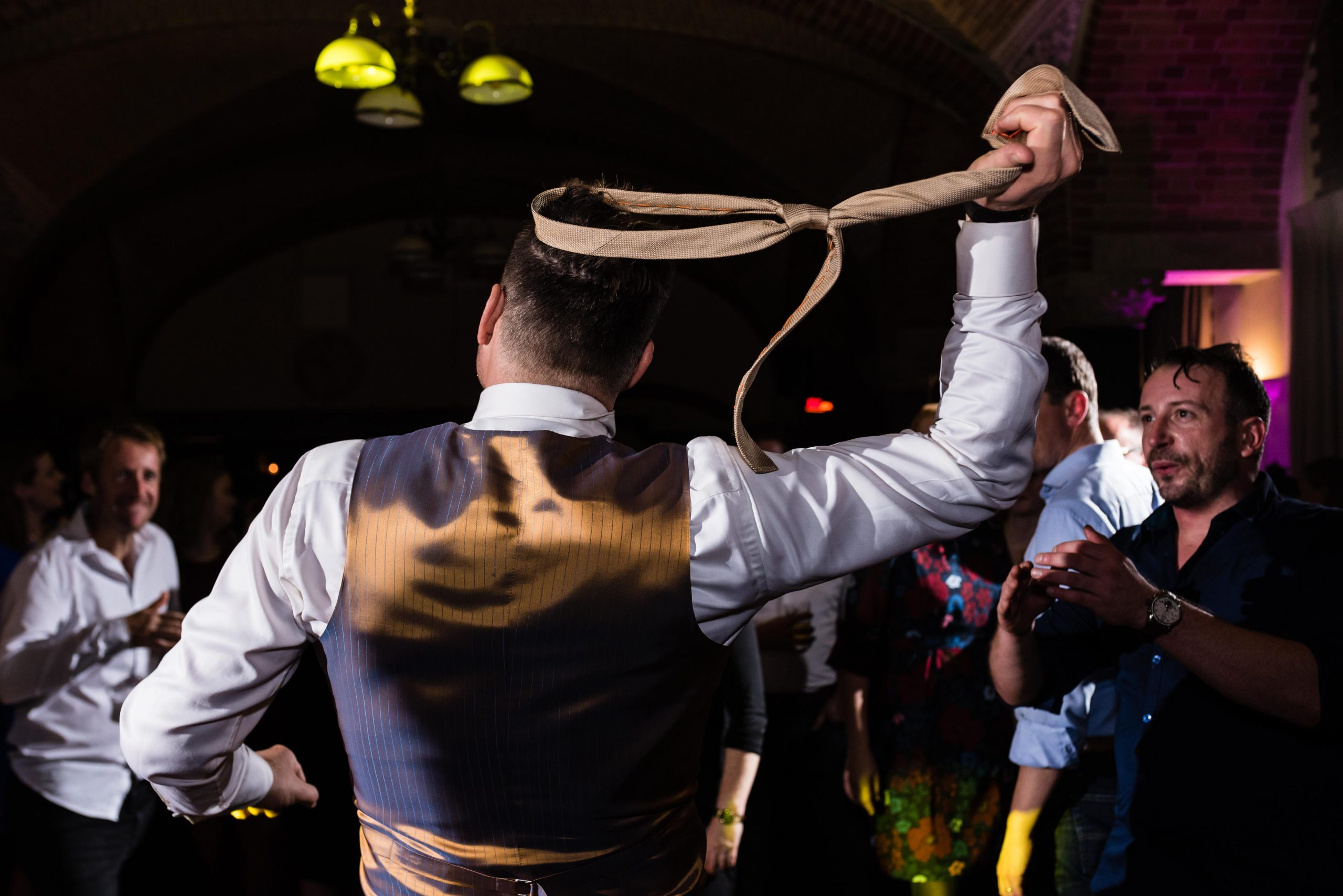 Bruidegom doet stropdas af tijdens het dansen.