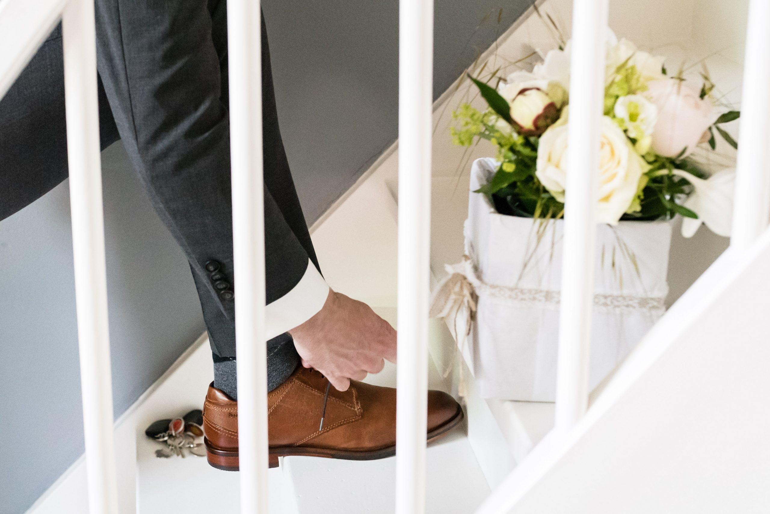 Bruidegom strikt zijn schoenen op de trap