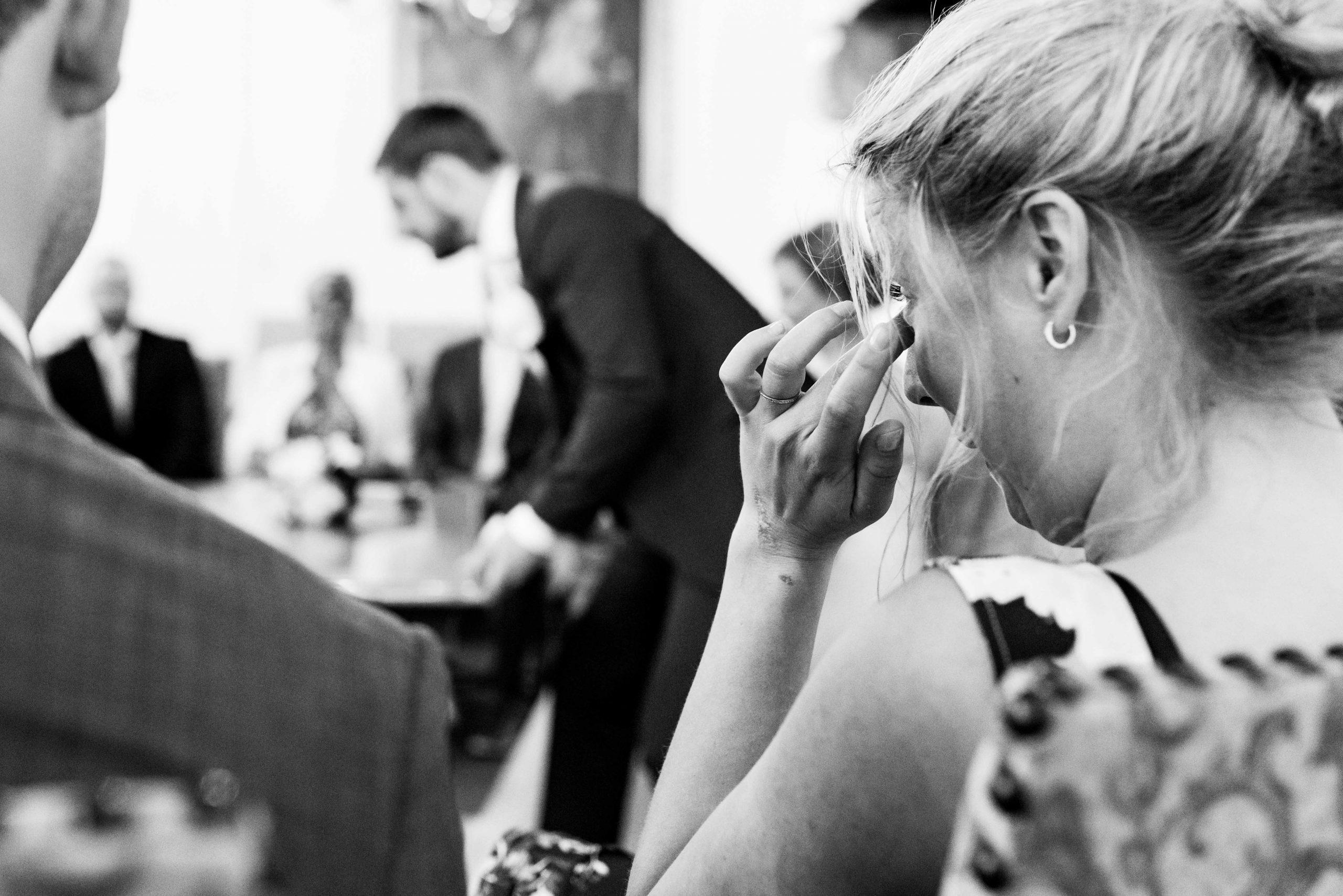 Zus pinkt traan weg tijdens trouwceremonie