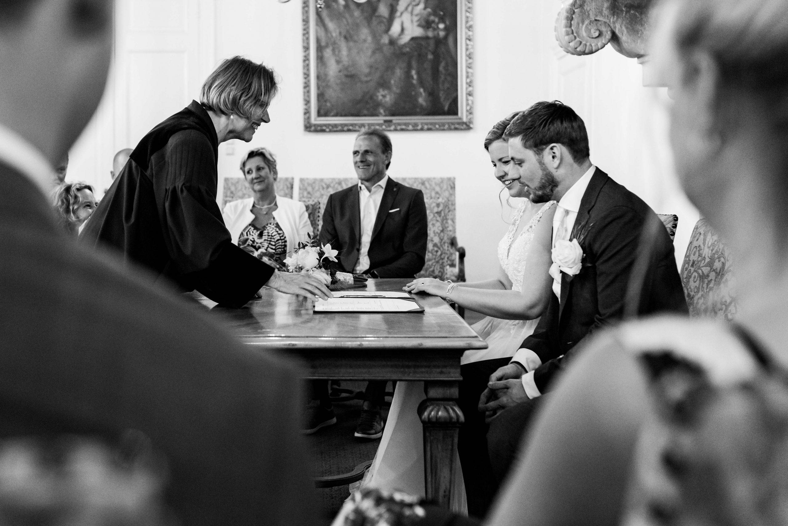 Bruid en bruidegom tekenen de akte