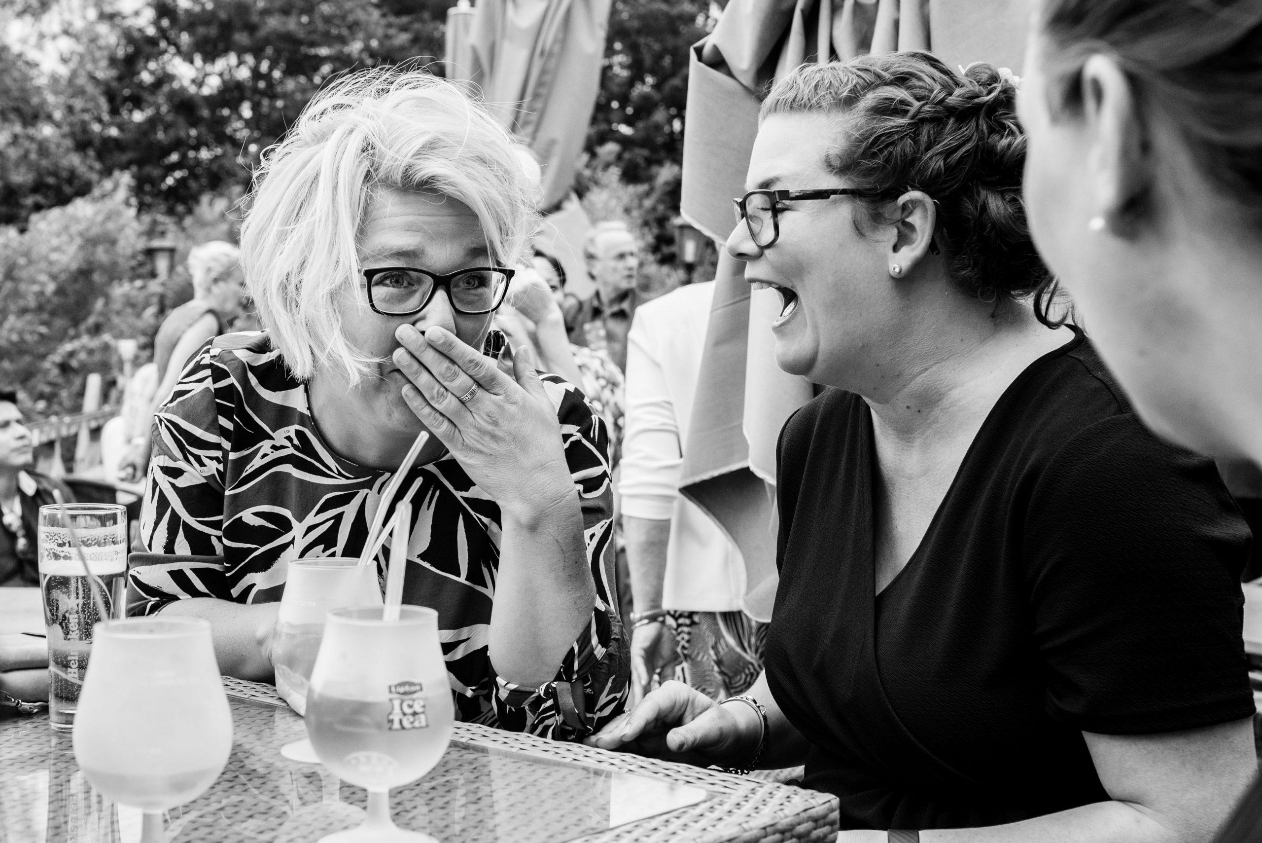 Gasten lachen hard op receptie bruiloft.