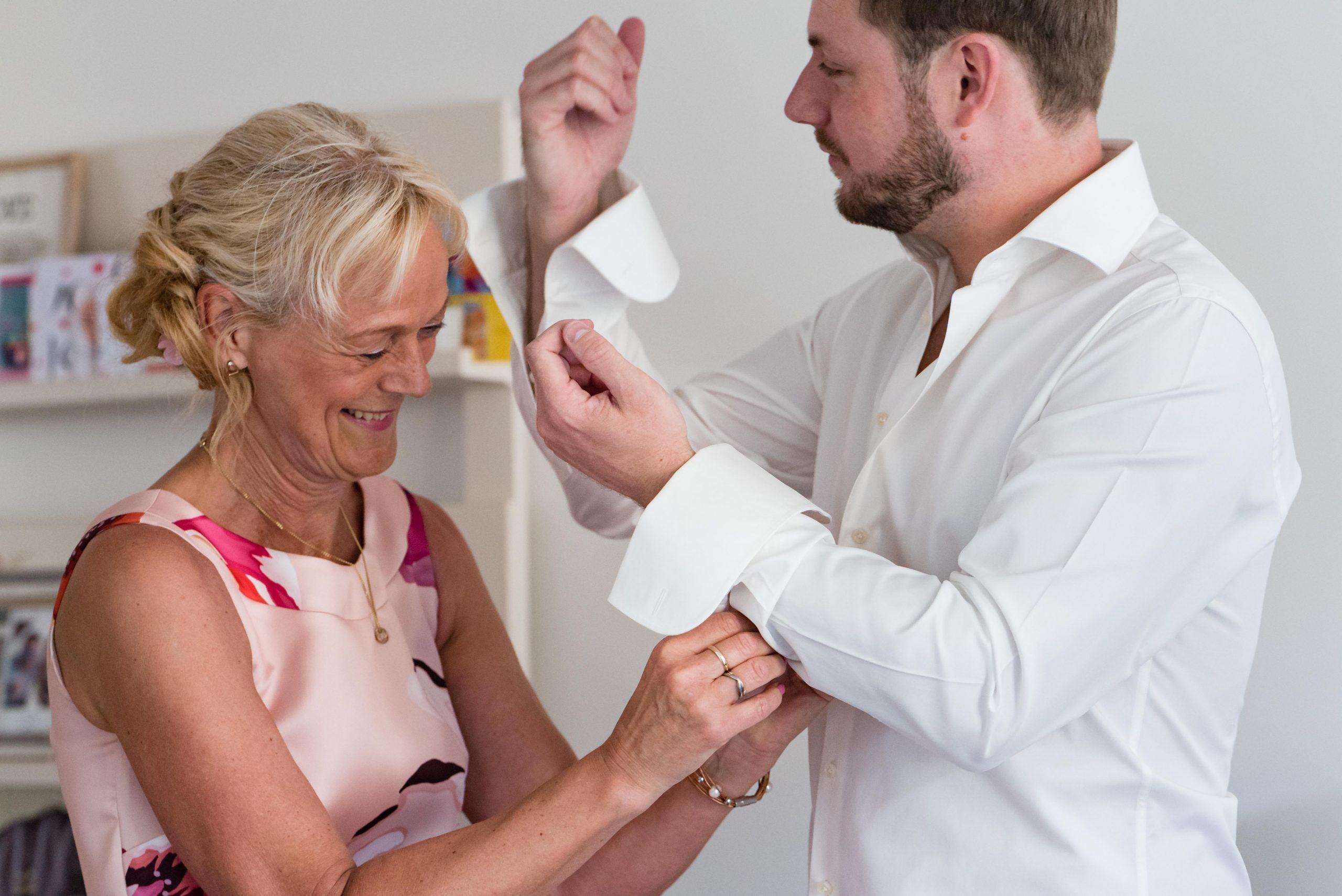 Moeder helpt bruidegom met manchetknopen.