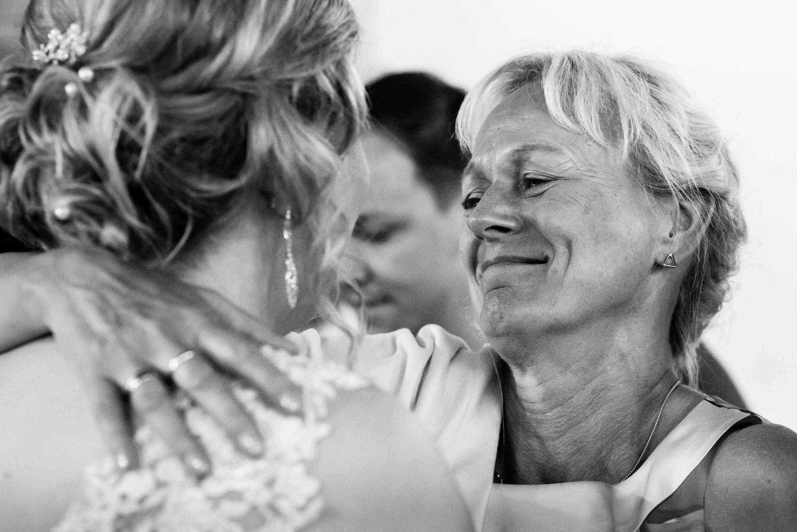 Moeder van de bruidegom feliciteert de bruid.