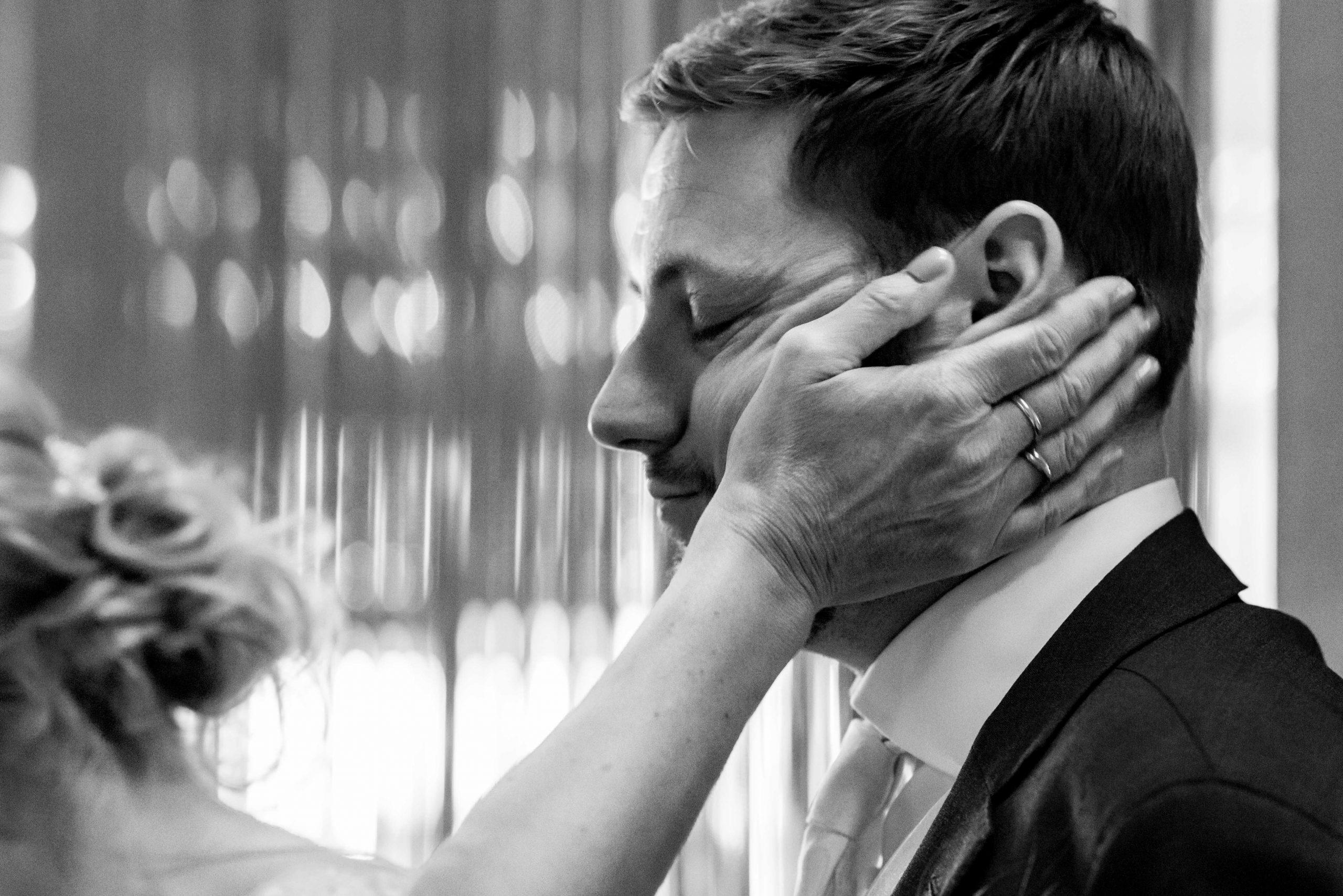 Liefkozende hand moeder op wang bruidegom.