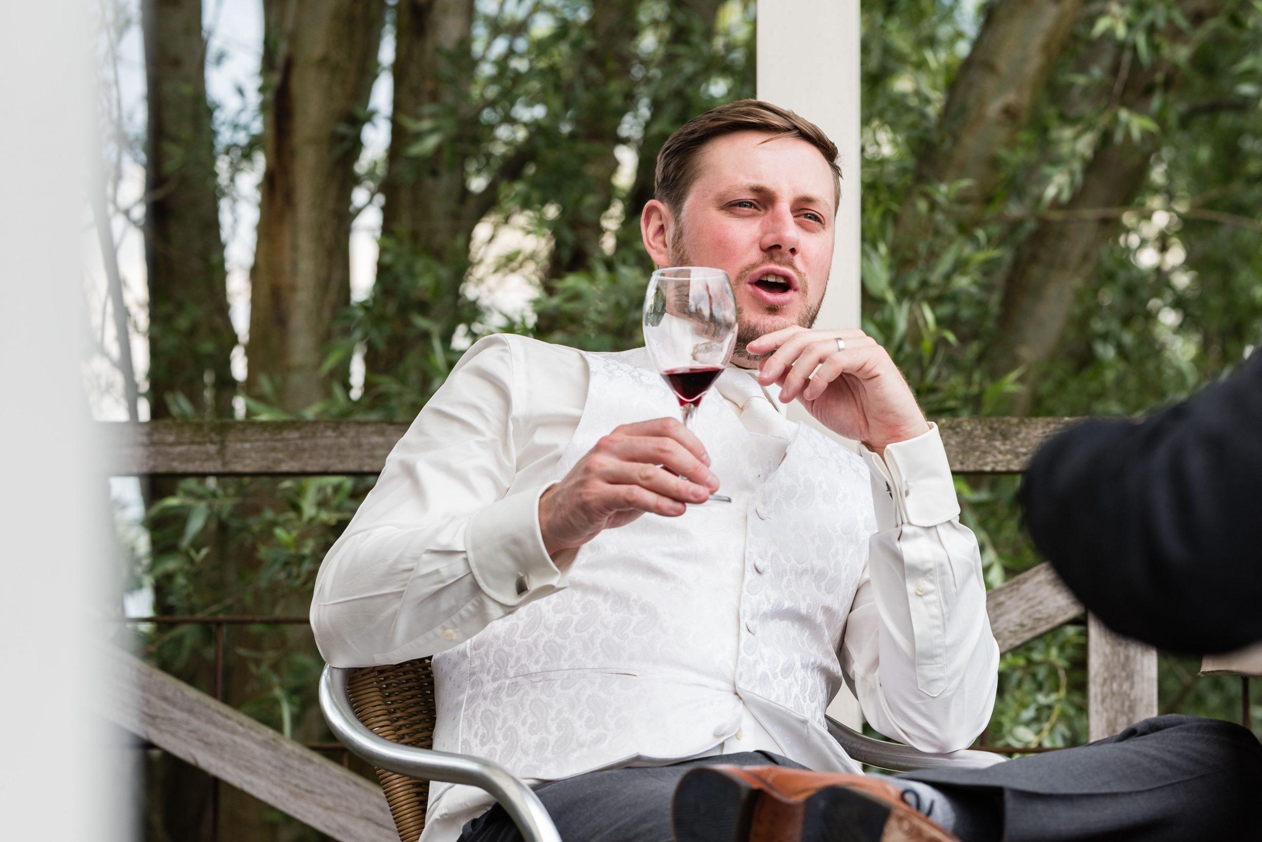 Bruidegom ontspant met een glas wijn op het terras.