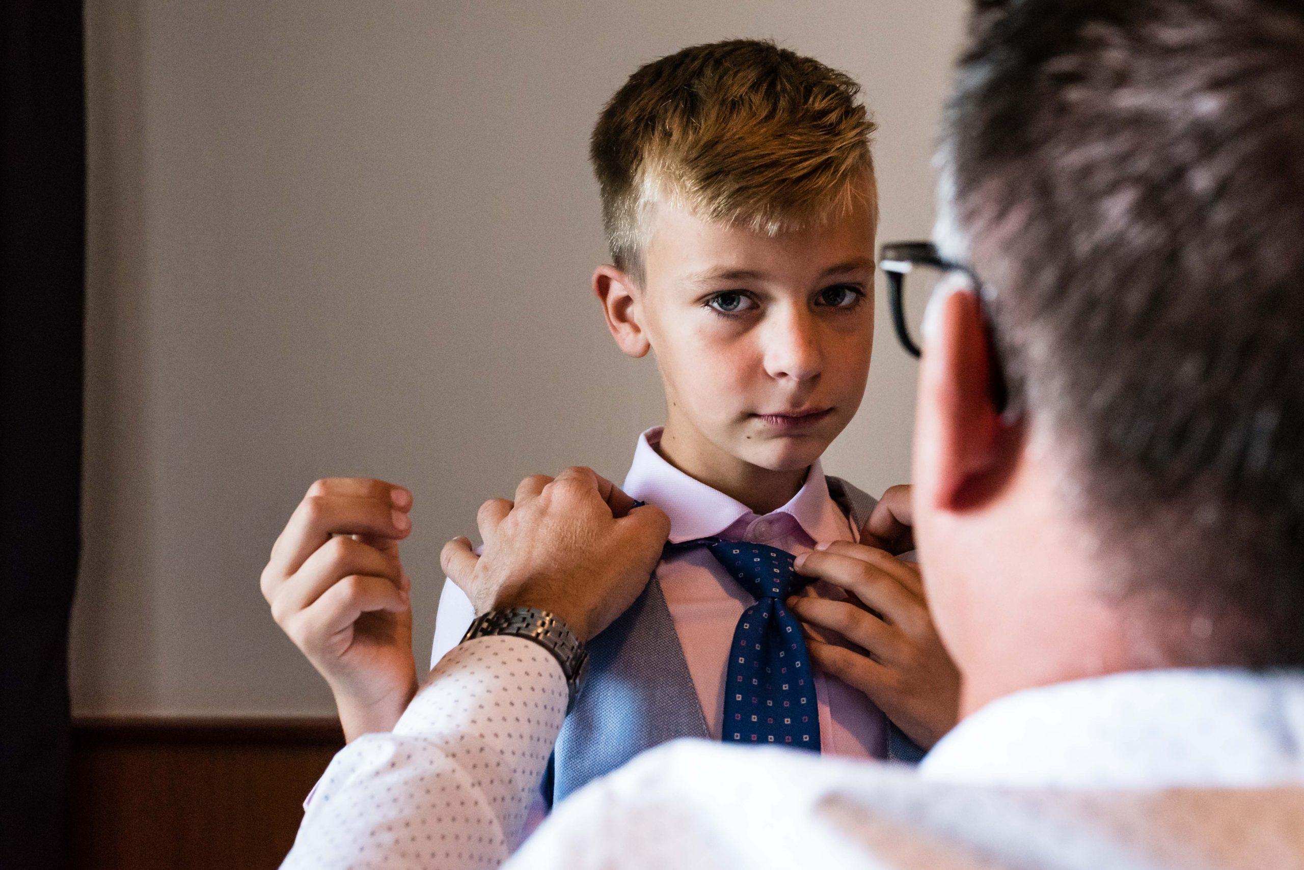 Bruidegom helpt zijn zoon met zijn stropdas.