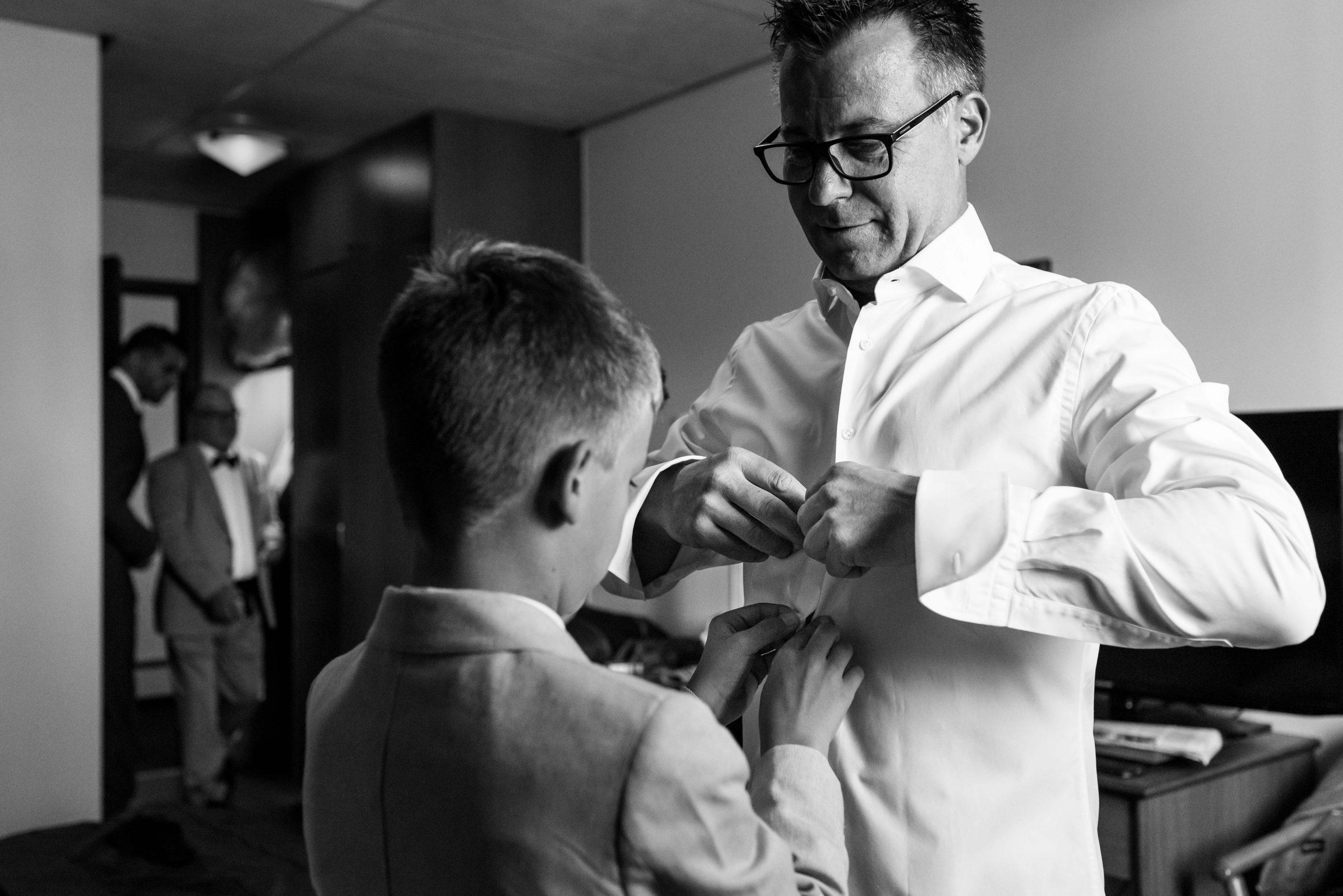 Bruidegom knoopt zijn overhemd dicht en zijn zoon helpt daarbij.