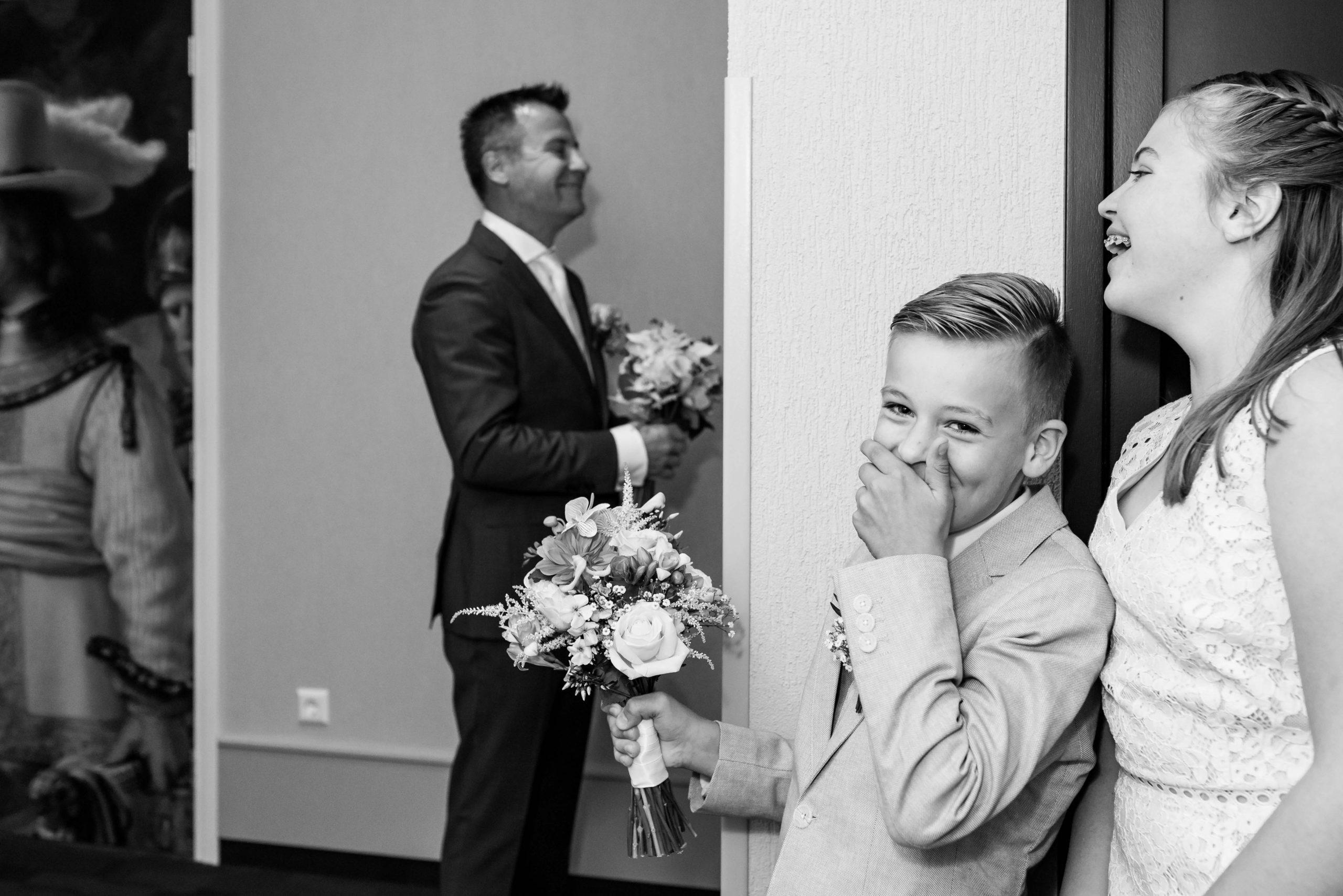 Bruidegom staat te wachten op zijn bruid en zijn kinderen lachen om zijn zenuwen.