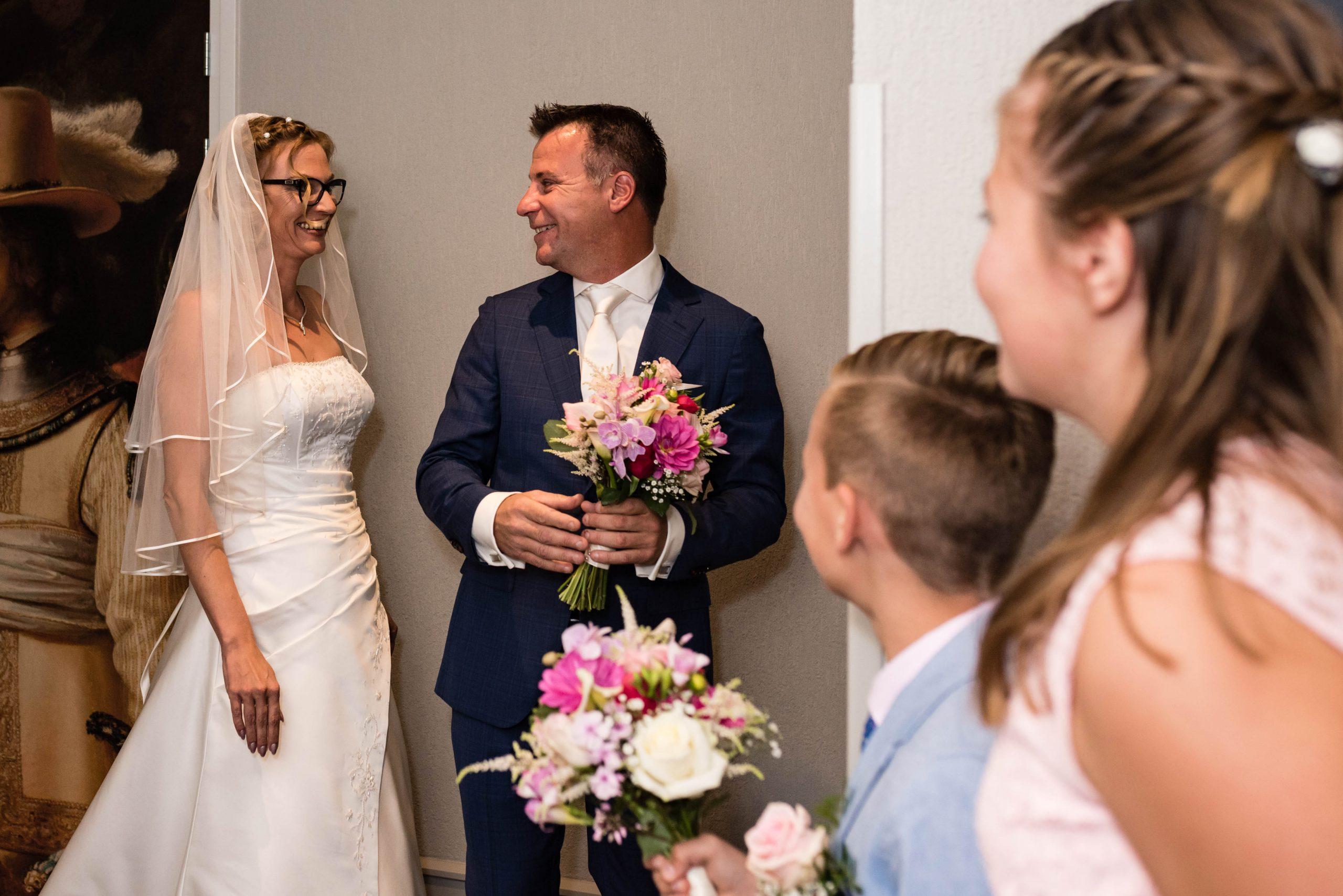 Bruidegom ziet zijn bruid voor het eerst en hun kinderen kijken om een hoekje toe.