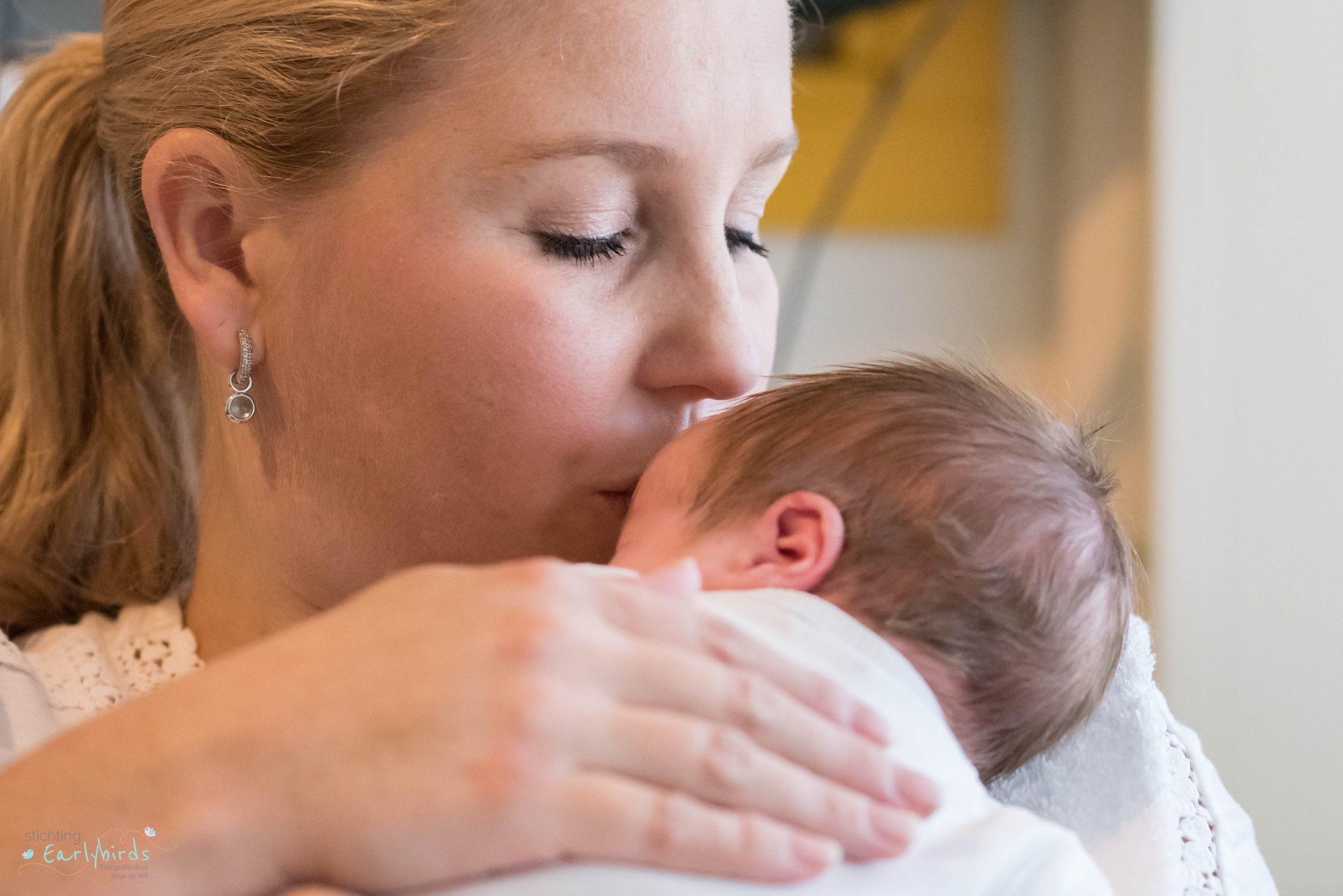 Moeder geeft haar baby een voorzichtige kus.
