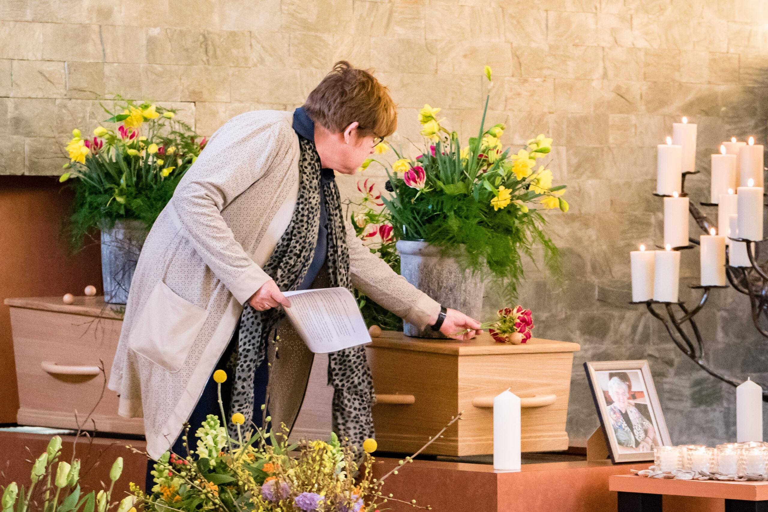 Dochter legt bloem op kist moeder Jasja de Wit afscheidsfotografie